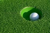 Minigolf ball in a hole closeup