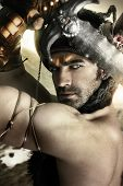 stock photo of sword  - Portrait of a sexy male model as ancient warrior with sword and helmet - JPG