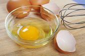 stock photo of chicken-wire  - Raw chicken eggs on wooden cutting board - JPG