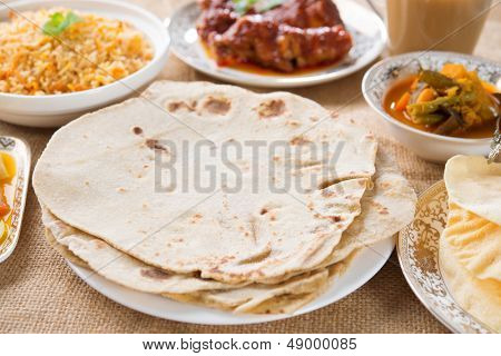 Chapatti roti, curry chicken, biryani rice, salad, masala milk tea and papadom. Indian food on dining table.