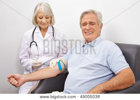 Man making a painful face at immunization shot at a doctors office