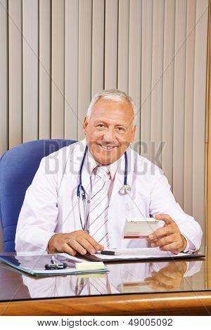 Lächelnd Arzt verschreiben Medikamente in seinem Büro