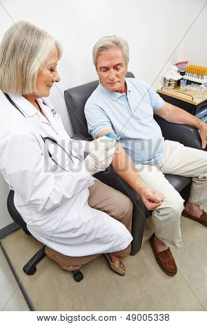Senior man with doctor at blood donation in a hospital
