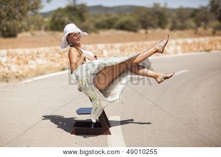 smiling girl is sitting on a road