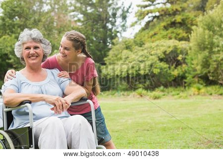 Granddaughter embracing grandmother in wheelchair in the park on sunny day