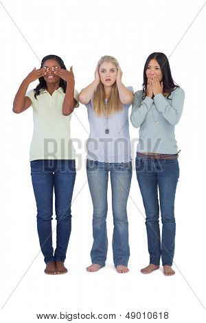 Young women acting out three wise monkeys on white background
