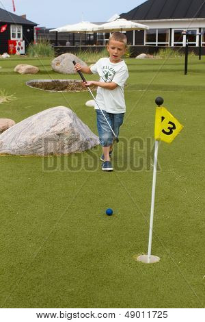 Boy Playing Minigolf During Summer