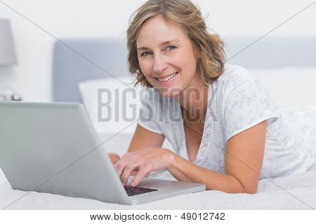 Smiling blonde woman lying on bed using laptop looking at camera in bedroom at home