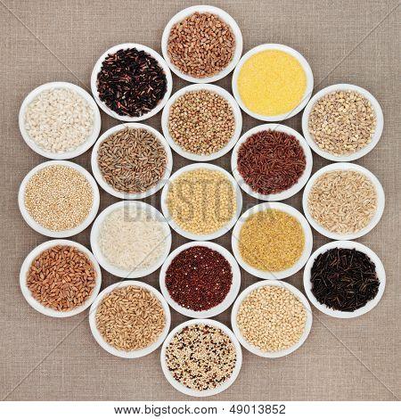 Large grain food selection in white porcelain bowls over hessian background.