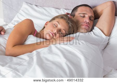 Attractive couple sleeping and cuddling in bed at home in bedroom