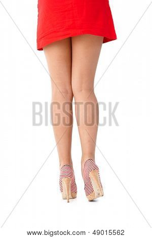 Sexy legs in red mini skirt and high heels photographed from behind.