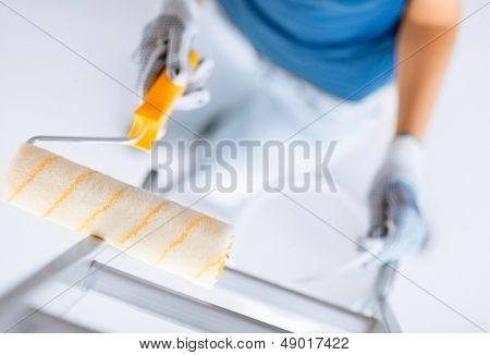 interior design and home renovation concept - woman with roller and paint pot