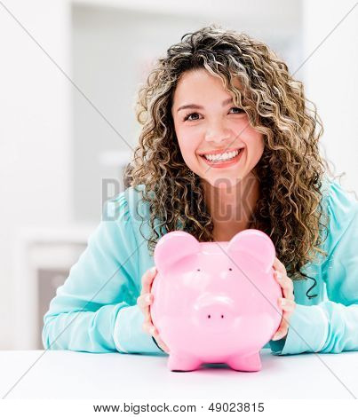 Happy woman saving money in a piggybank and smiling