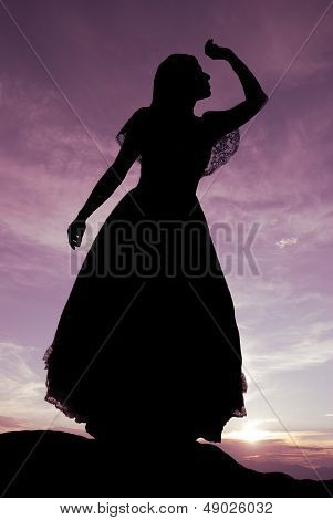 Silhouette of woman on hill overlooking valley with purple hues