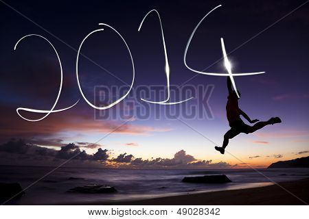 Happy New Year 2014.young Man Jumping And Drawing 2014 By Flashlight