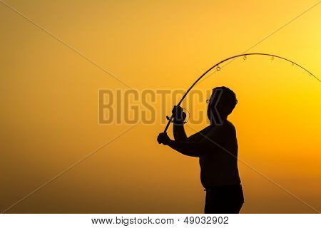 Fisherman's silhouette on the beach at colorful sunset