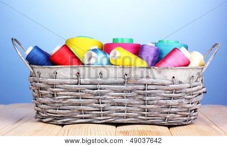 Bright threads in basket on wooden table on blue background