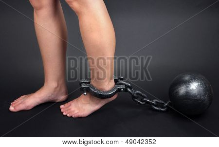 Legs in heavy iron shackles on grey background