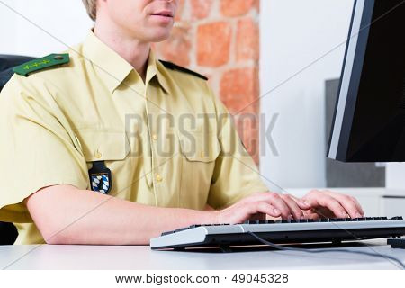 Police officer in police department working on the computer, on a case or registering a complaint