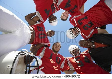 Low angle view of rugby players with coach forming huddle against clear sky