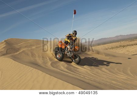 Low angle view of a man riding quad bike in desert on a sunny day