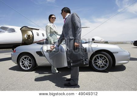 Businessman holding door of convertible for colleague on landing strip near private aircraft