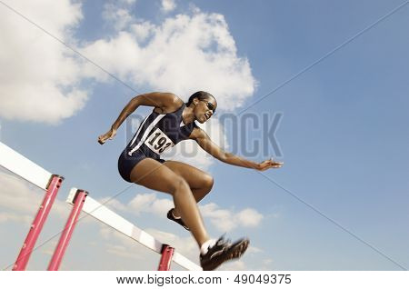 Low angle view of a female athlete jumping hurdle