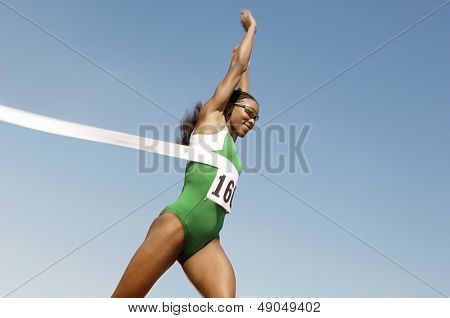 Side view of a female runner winning race against the blue sky