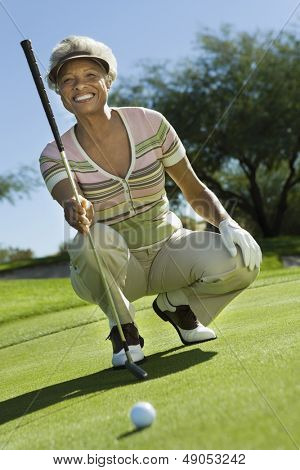 Portrait of a smiling senior woman crouching on golf course