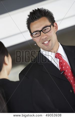 Smiling businessman using hands free device while talking to female colleague