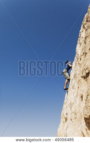 Side view of a young man free climbing on cliff against clear blue sky