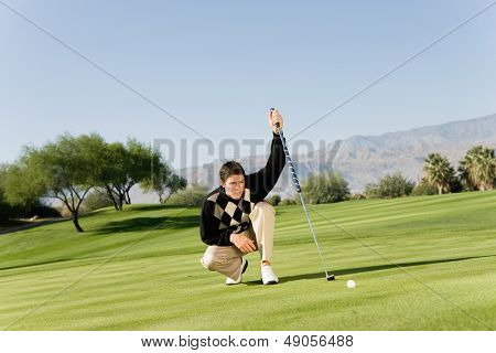 Male golfer on golf course lining up putt on green