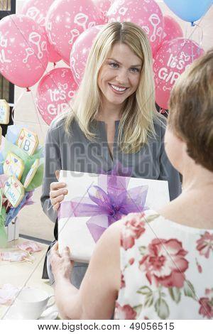 Happy blond Woman Geschenk von ihrer Mutter auf Baby-Dusche erhalten