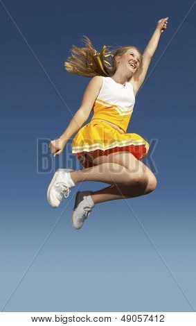 Low angle view of a cheerleader in yellow costume jumping midair against clear sky