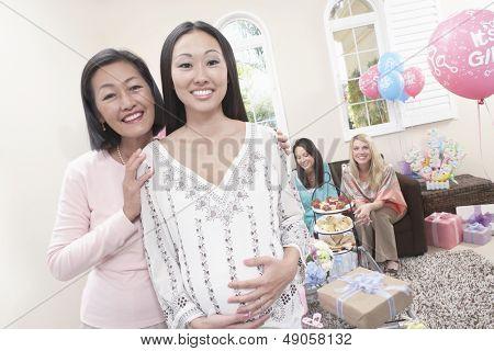 Portrait of smiling Mutter und schwangere Tochter mit Freunden auf Baby-Dusche