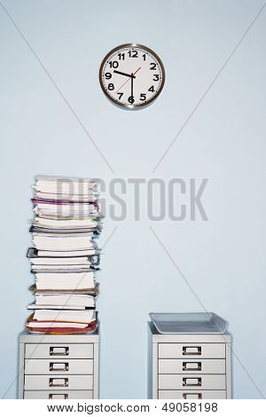 Office wall with clock stack of paperwork in inbox on file cabinet
