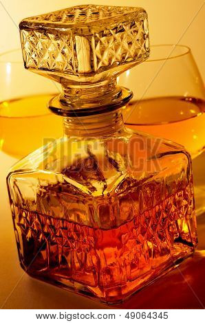 closeup of a vintage glass liquor bottle and some cognac glasses with liquor