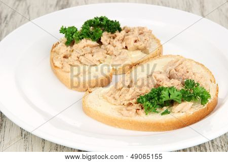 Tasty sandwiches with tuna and cod liver sardines, on white plate. on wooden background