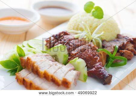 Roasted duck, roasted pork crispy siu yuk and Charsiu Chinese style, served with steamed rice on dining table. Singapore cuisine.