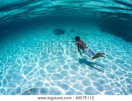Young man diving on a breath hold in a tropical sea