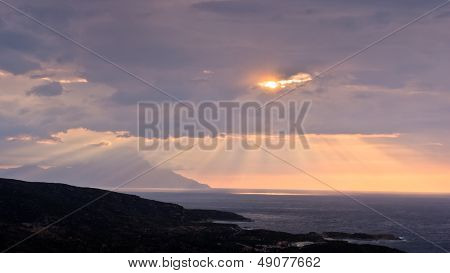Divine light, stormy sky and sunrise on a landscape around holy mountain Athos