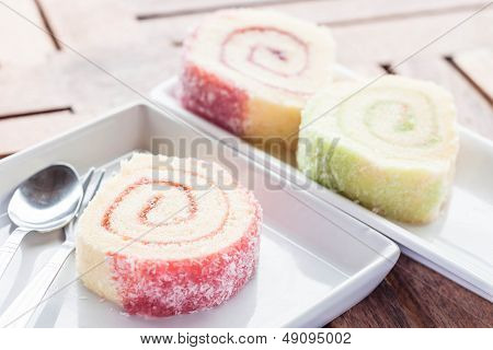 Colorful Jam Rolls On White Dish With Spoon And Fork