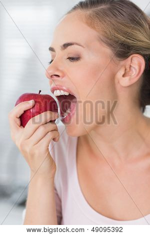 Pretty woman in her kitchen munching apple in close up