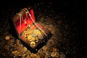 stock photo of treasure chest  - Scattering of coins around and inside trunk with treasure - JPG