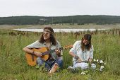 stock photo of independent woman  - young hippie men play on the guitar and sing young hippie woman make a wreath of flowers - JPG