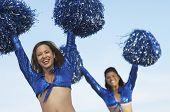 stock photo of pom poms  - Portrait of two happy cheerleaders with pom poms raised against the sky - JPG