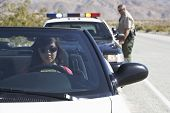 View of an Asian woman sitting in car being pulled over by police officer on desert road