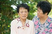 picture of condolence  - Candid shot of an Asian mature woman consoling her crying old mother at outdoor natural green park - JPG