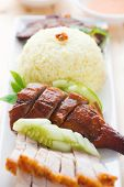Roasted duck and roasted pork crispy siu yuk, Chinese style, served with steamed rice on dining tabl