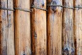 stock photo of log fence  - A fence made of logs bound with rope - JPG